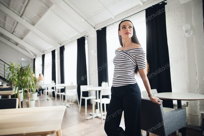 Thumbnail for Beautiful brunette girl standing in cafe near wooden table. Well-groomed woman sitting in modern
