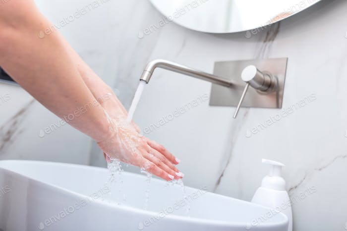 Woman washing hands with foam soap. Hygiene, preventing coronavirus