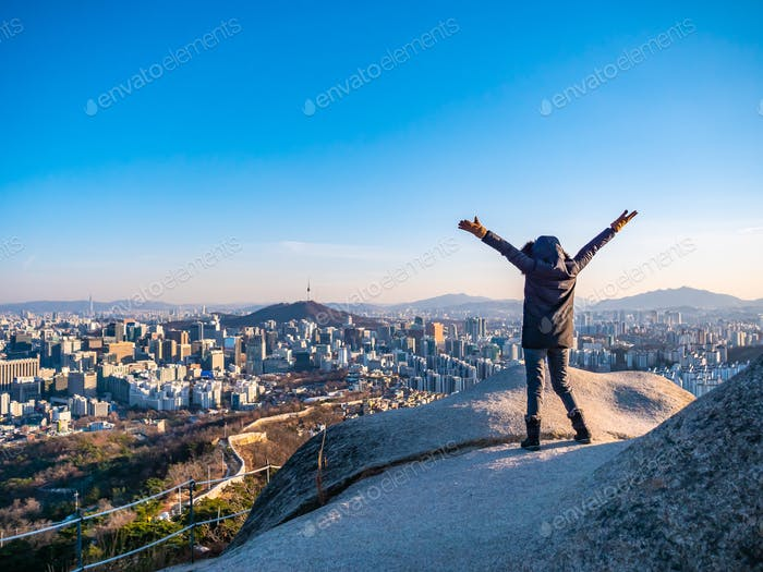 Woman or Girl on the top of mountain with beautiful cityscape Se