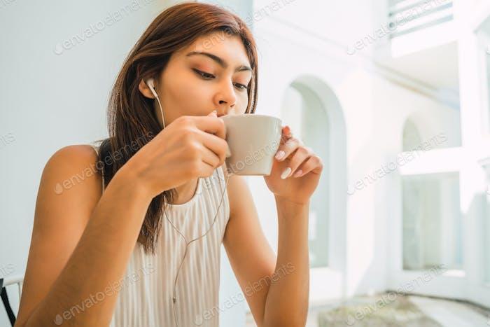 Mujer joven bebiendo una taza de café en la cafetería.