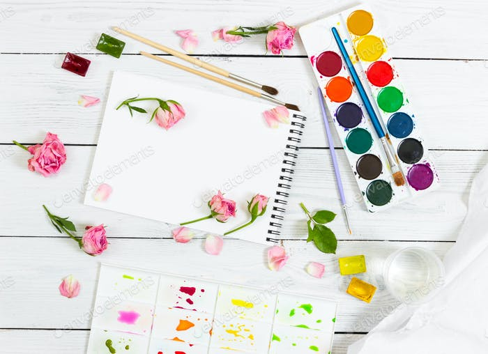 Sketchbooks, brushes, watercolor paints, palette and pink roses.