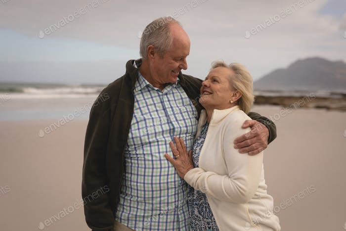 Front view of active senior couple embracing each other at the beach. They seem happy.