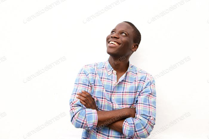 Cheerful young black man with arms crossed and looking up