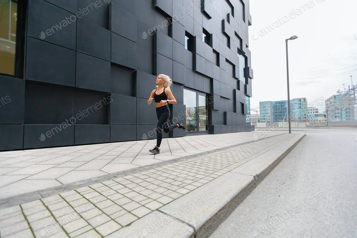 Focused fast running woman wearing sports top in modern city environment