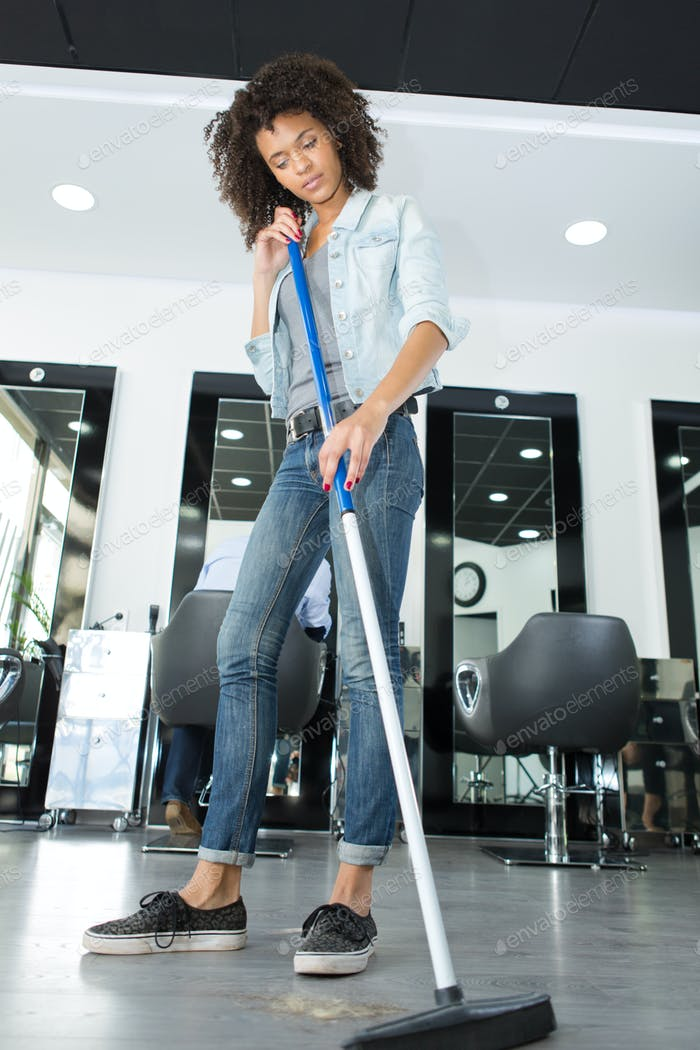 worker floor cleaning at a hairdressers