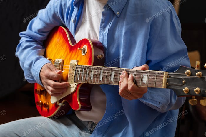 Thumbnail for Young man playing guitar, close up view, dark background