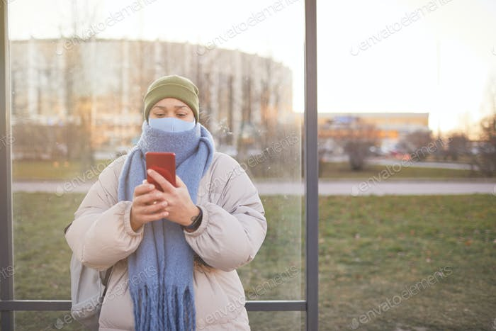 Woman standing on bus stop