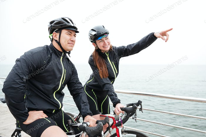 Happy woman cyclist showing finger on something