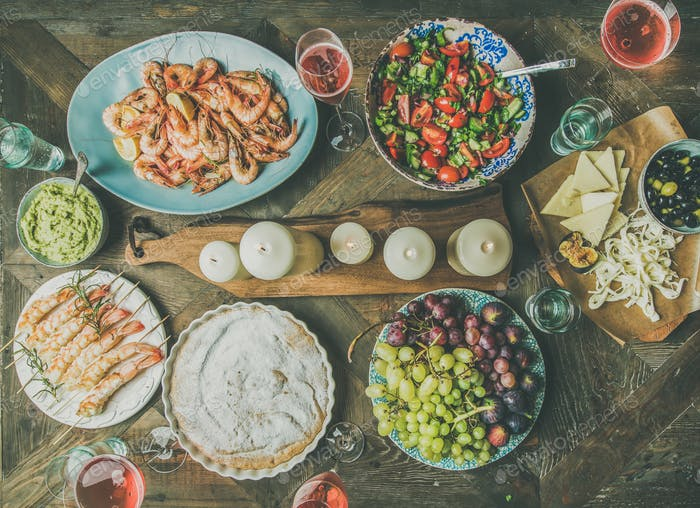 Flat-lay of salad, shrimps, olive, grape, cake over wooden background