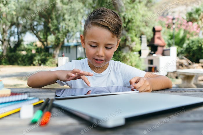 Kid with tablet studying in garden