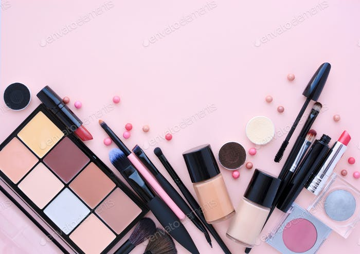 Makeup brush and decorative cosmetics on a pastel pink backgroun