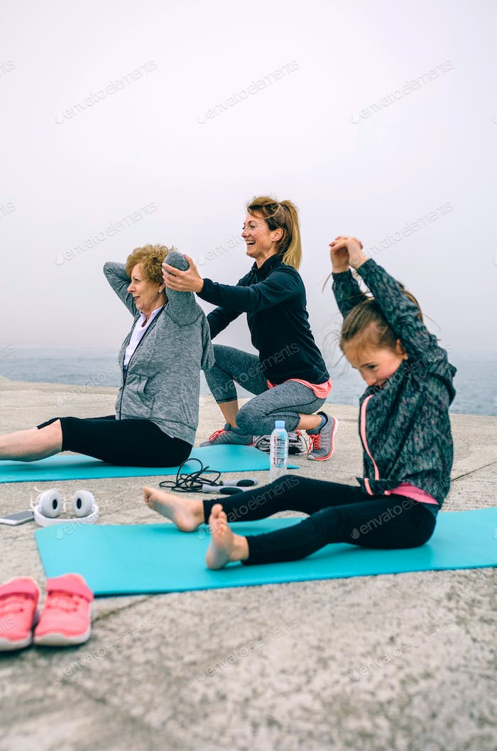 Women exercising with little girl