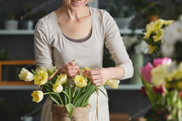 Woman decorating bouquet of tulips