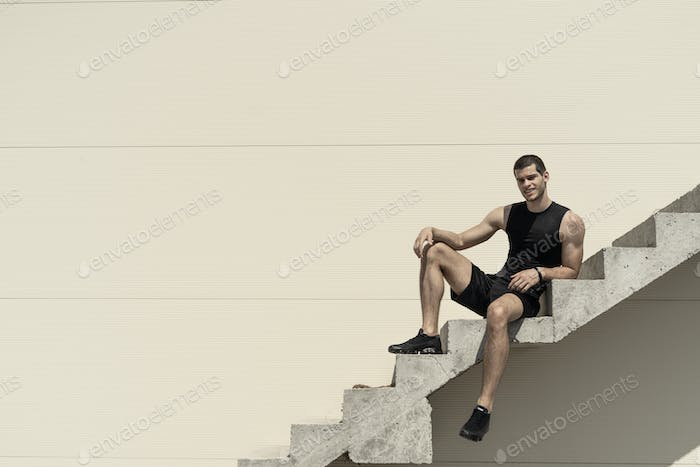 Athletic carefree sportsman posing while sitting and smiling on stairs