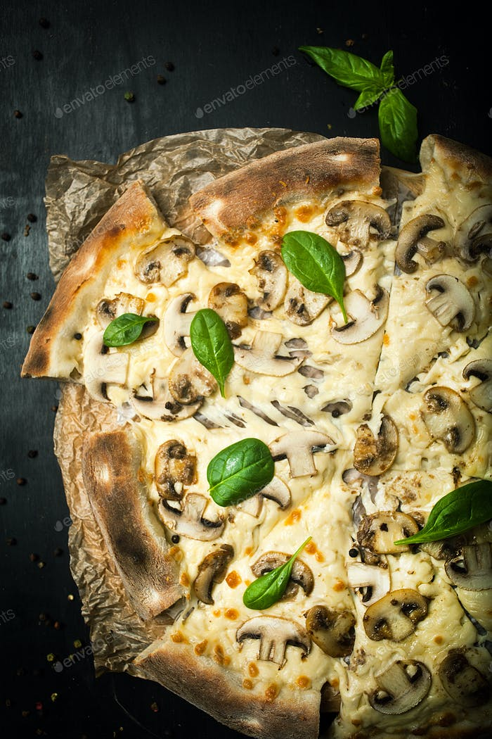 Tasty pizza with mushrooms and cheese and basil leaves