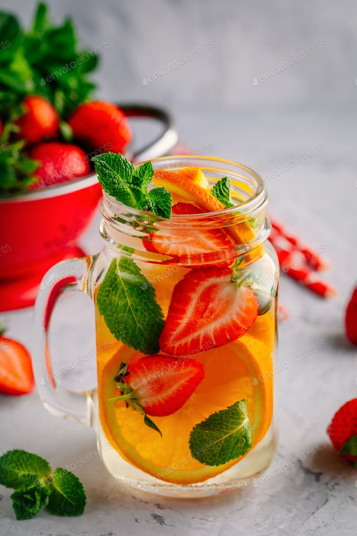 Infused detox water with orange, strawberry and mint. Ice cold summer cocktail or lemonade.