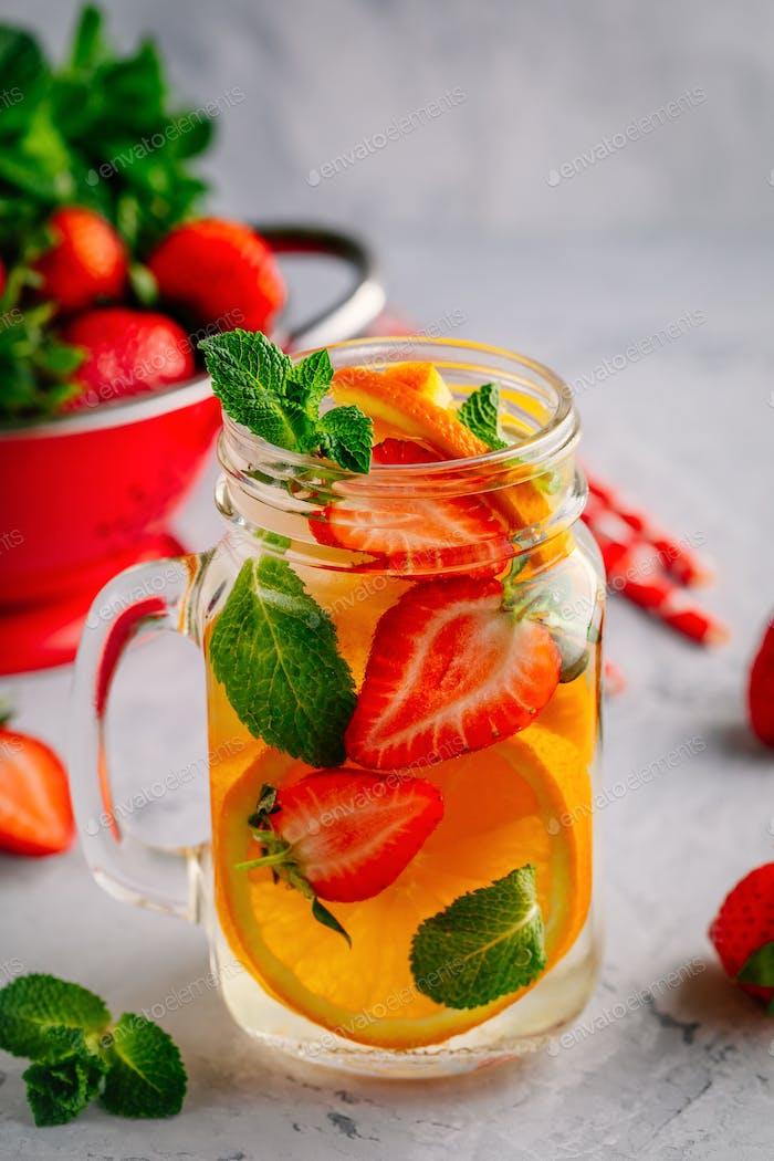 Infusion Detox Wasser mit Orange, Erdbeere und Minze. Eiskalter Sommercocktail oder Limonade.