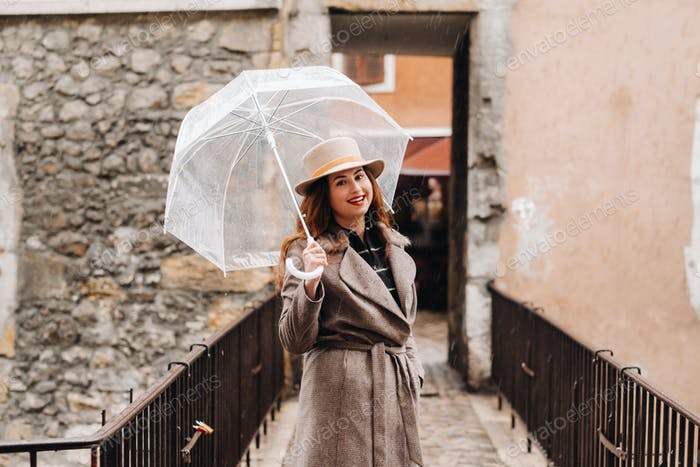 beautiful romantic girl in a coat and hat with a transparent umbrella in Annecy. France. The girl in