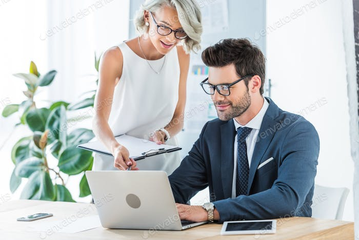 young smiling managers looking at laptop in office