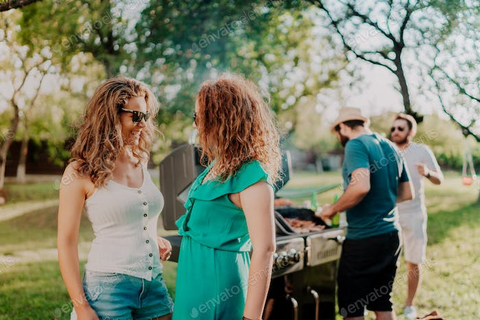 Girls wearing sunglasses, smiling and laughing at barbecue outdoor party, backyard summer concept