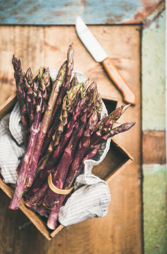 Fresh raw uncooked purple asparagus over rustic background, selective focus
