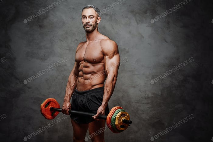 Buffed sportsman posing in a dark studio with a barbell