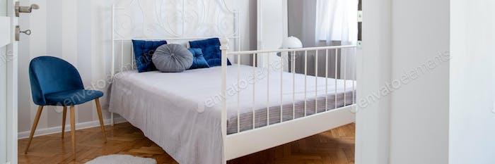 Trendy blauen Stuhl neben King-Size-Bett mit Kissen im eleganten Schlafzimmer Interieur