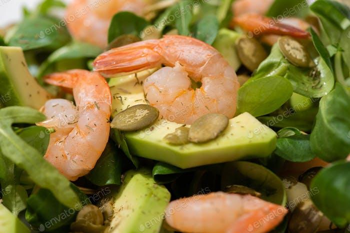 Nahaufnahme Blick auf frischer grüner Salat mit Kürbiskernen, Garnelen und Avocado
