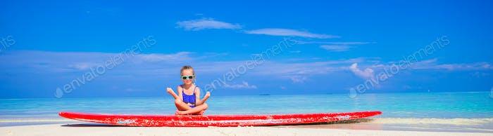 Little girl in yoga position meditating on surfboard