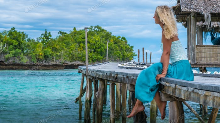 Girl Sitting on Wooden Pier of an Homestay looking into blue ocean, Bamboo Hut in background, Gam