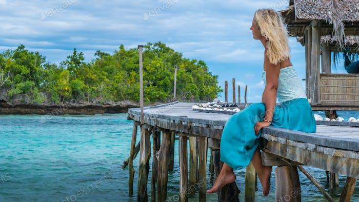 Mädchen sitzt auf Holz Pier einer Homestay Blick in blauen Ozean, Bamboo Hut im Hintergrund, Gam