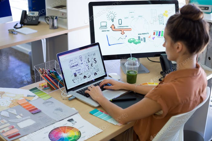 Female executive working over laptop at her desk