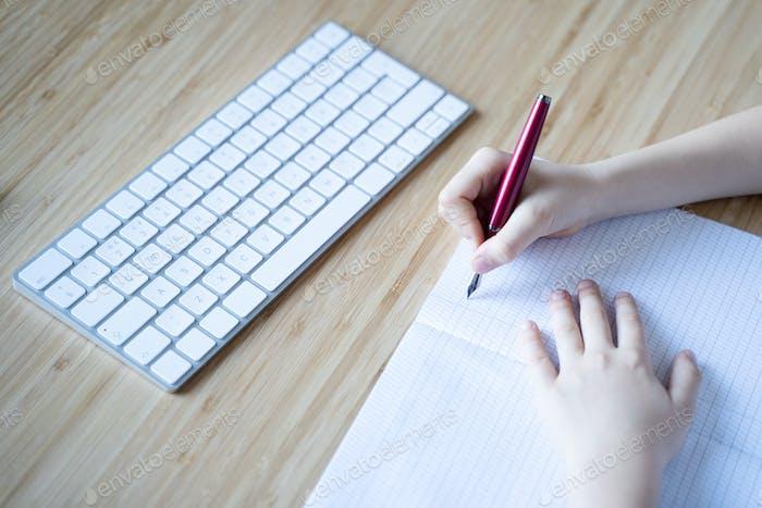kleines Mädchen Schreiben mit Füllfederhalter in ihrem Notizbuch