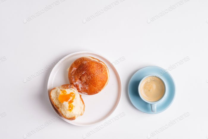 Homemade baked donut on a white ceramic plate and cup of coffee on a light grey background. Flat lay