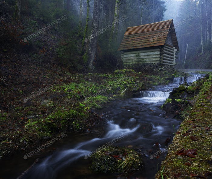 Small house stands on the banks of a mountain river