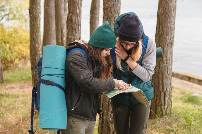 Two young tourist determine the route map and compass