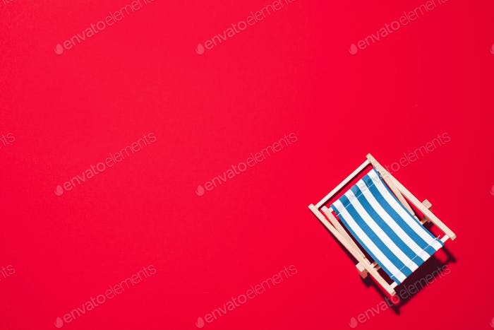 Deck chair with hard shadow on red paper background. Flat lay and copy space. Summer travel vacation