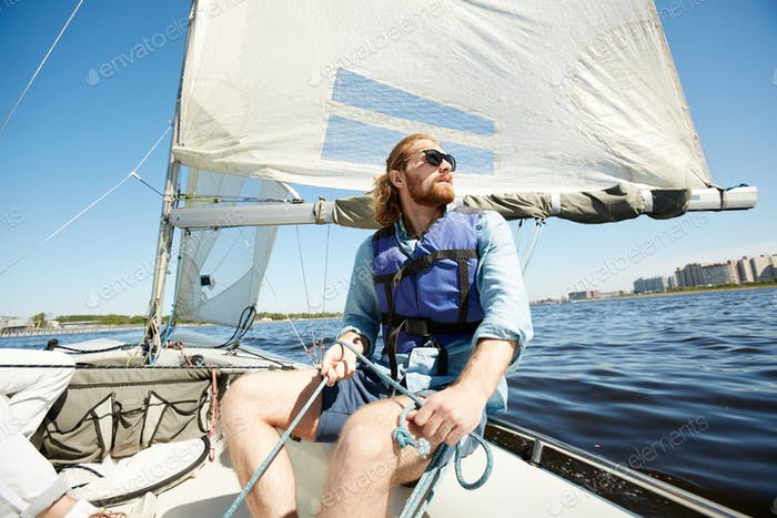 Pensive man with rope on sail boat