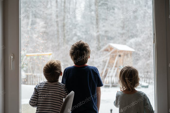 Kids looking out the window while snowing