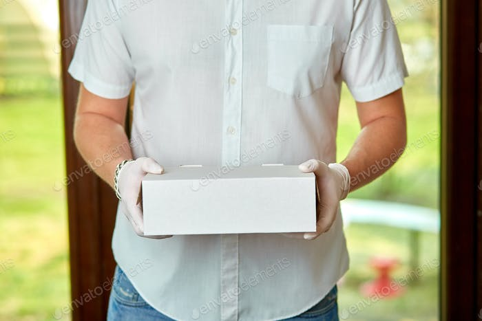 Courier, delivery man in medical latex gloves and mask safely delivers online