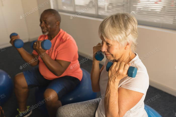 Side view of active senior people exercising with dumbbells at home