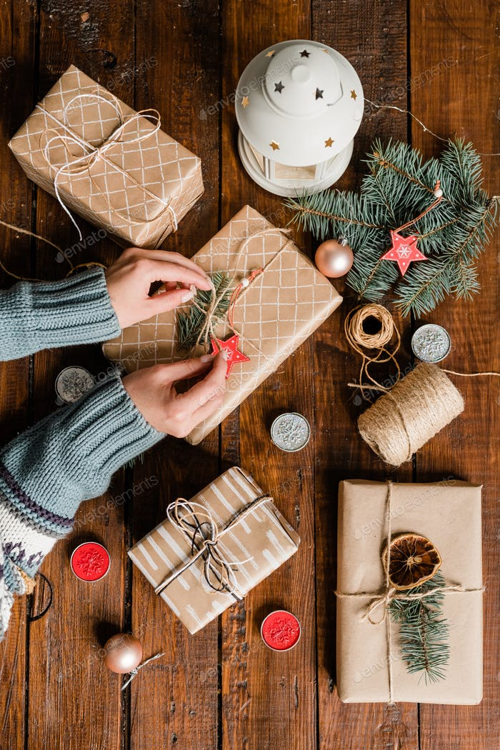 Overview of young woman hands making knot on top of packed and wrapped giftbox