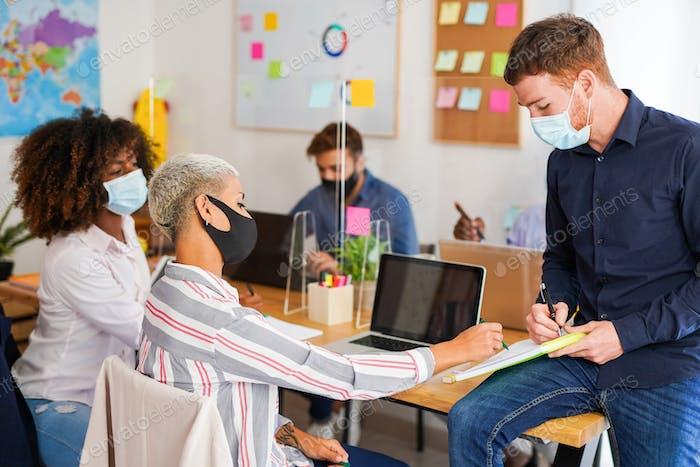 Personas multirraciales en una oficina de coworking con medidas de seguridad para el coronavirus