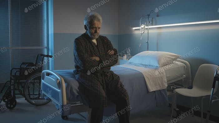 Depressed senior sitting on the hospital bed alone