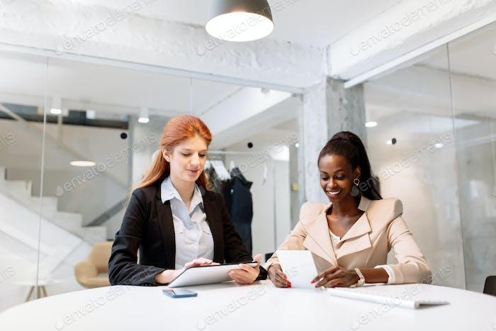 Dos mujeres de negocios atractivas que Uso la Tecnología