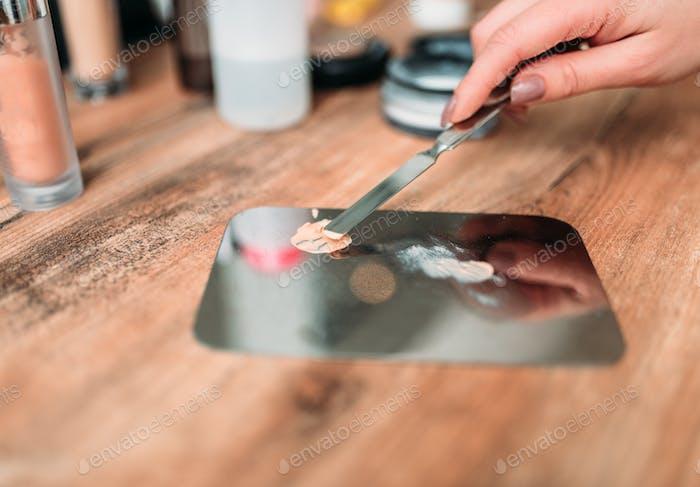 Female make up artist hand prepares cosmetics