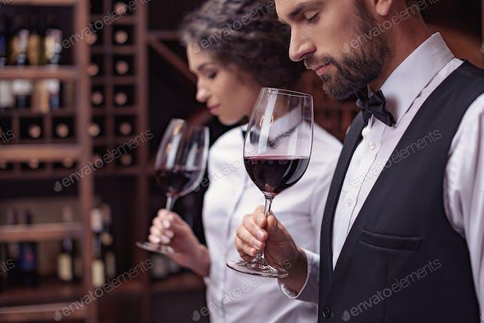 Zwei Sommeliers, männliche und weibliche Verkostung Rotwein im Keller