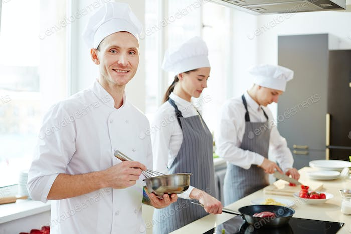 Happy chef using whisk