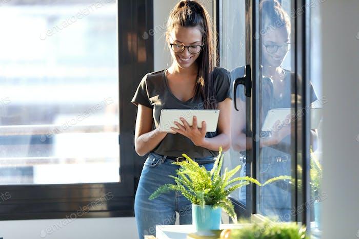 Lächelnd junge Geschäftsfrau mit ihrem digitalen Tablet im Büro.