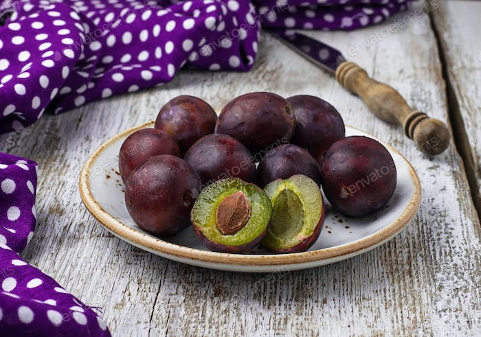 Sweet fresh plums on wooden table